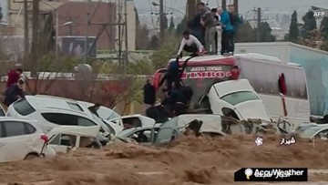 People climb onto vehicles tossed around by powerful floodwaters to escape drowning