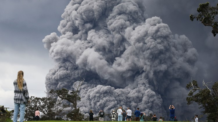 People watch at a golf course as an ash plume rises in the distance from the Kilauea volcano on Hawaii's Big Island on May 15, 2018 in Hawaii Volcanoes National Park, Hawaii.