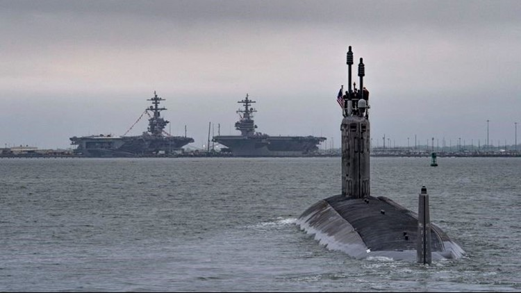 The submarine  Indiana  departs for its first set of sea trials with two HII-built aircraft carriers visible in the distance at Norfolk Naval Station.