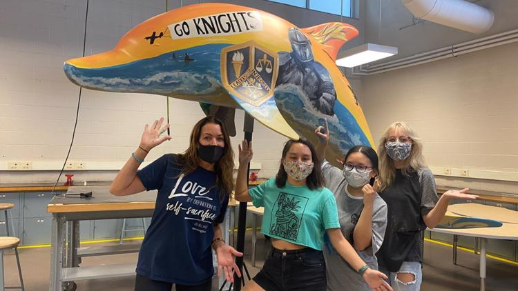 MAKING A MARK: Students decorate dolphin statue in support of Operation Smile